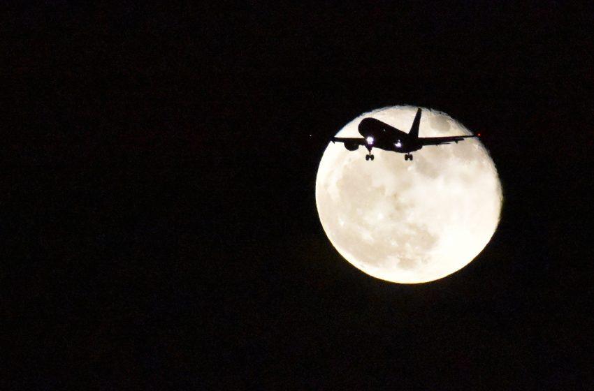 Luna in sfondo ad un aereo in volo